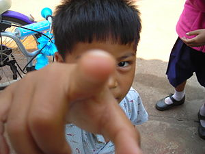 English: Thai boy pointing to the viewer.