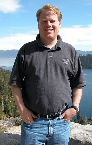 Pic of Robert Scoble, a white man with blond hair of about 40, wearing jeans and a blue polo shirt, with a lake and hills in the background