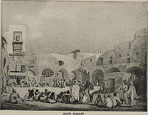 English: People sitting in the courtyard of a ...