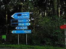Schilder bei Voeren / Fourons. Jemand hat die niederländischsprachigen Städtenamen durchgestrichen.
