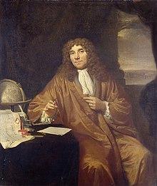 painting of Antonie van Leeuwenhoek, in robe and frilled shirt, with ink pen and paper