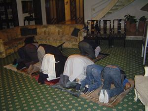 English: Line of men bending in Muslim prayers...
