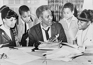 Bayard Rustin (center) speaking with (left to ...