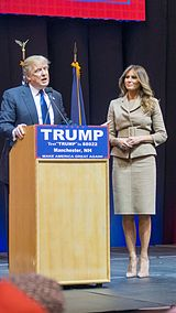 "Donald and Melania Trump standing behind a blond-wood podium with the words ""TRUMP"", ""TEXT 'TRUMP' TO 88022"", ""MANCHESTER, New Hampshire"", and ""MAKE AMERICA GREAT AGAIN"" printed in white-on-blue text from top to bottom. Donald is to the left, behind the actual podium. Melania is about three feet to his left."