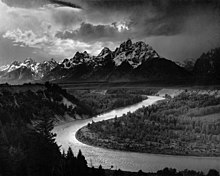 A dramatically-lit black-and-white photograph depicts a large river, which snakes from the bottom right to the center left of the picture. Dark evergreen trees cover the steep left bank of the river, and lighter deciduous trees cover the right. In the top half of the frame, there is a tall mountain range, dark but clearly covered in snow. The sky is overcast in parts, but only partly cloudy in others, and the sun shines through to illuminate the scene and reflect off the river in these places.