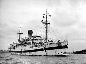 """A single-funnelled merchant ship at rest. The ship is painted white, with a dark horizontal band along the hull, interspersed by dark crosses. The number """"47"""" is painted near the bow, in a black box above the line."""