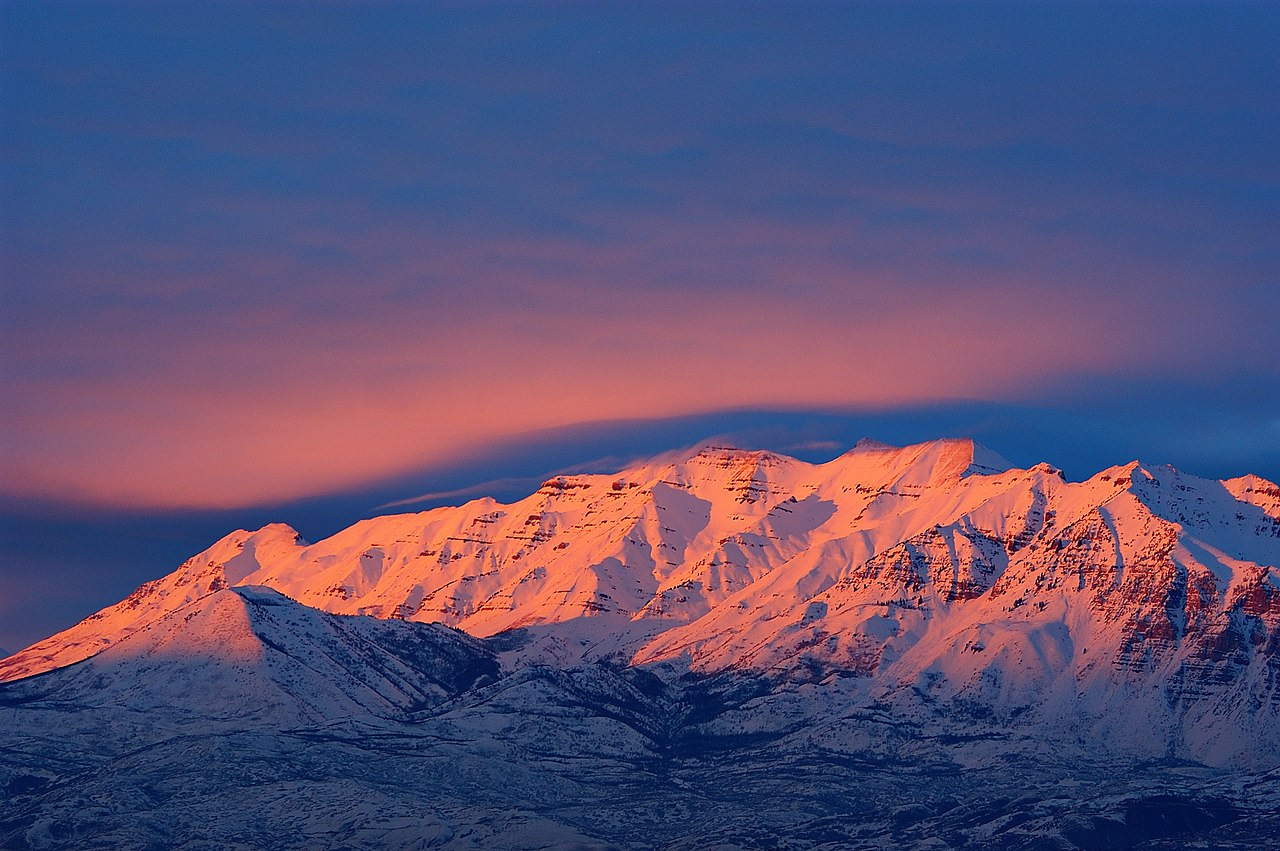 Mount Timpanogos at sunset.  Timpanogos is the second highest mountian in the Wasatch Front (11,752 ft/3,582 m), and forms the eastern border of Utah County.  Wikipedia image, photo by Eric Ward from Provo, UT, USA - Mount Timpanogos - 01/19/08