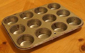 A cupcake pan, made of tinned steel.