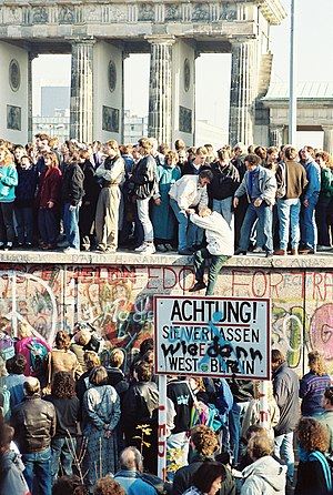 People atop the Berlin Wall near the Brandenbu...