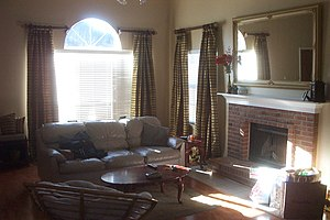 English: A den or family room with a sofa or c...