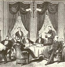 Dessin noir et blanc montrant des civils et des militaires, certains assis, d'autres debouts, autour d'une table, examinant et discutant les documents objets du traité.