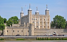 A keep seen from a river, rising behind a gate. The keep is large, square in plan, and has four corner towers, three square and one round, all topped by lead cupolas.