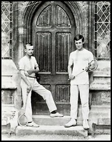 Two schoolboys holding racquets, standing on wooden steps either side of an arched wooden double door to a school building