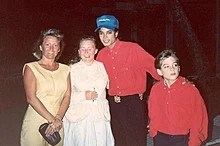 A smiling Jackson wears a blue baseball cap and a red shirt. On his right are two women. One holds a pen, and one a small purse. On his left a young boy looks off-camera. He is dressed in a red shirt too. Jackson's hand is on his shoulder.