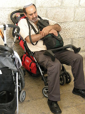 An exhausted father uses a pram