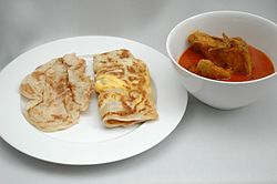 Plain roti prata (left) and egg roti telur (centre), with a bowl of chicken curry on the side