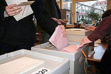 Stimmabgabe in der Wahlurne (von WikimediaCommons, Details bei Anklicken des Bildes)