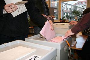 Deutsch: Stimmabgabe: Wählerin wirft Stimmzett...