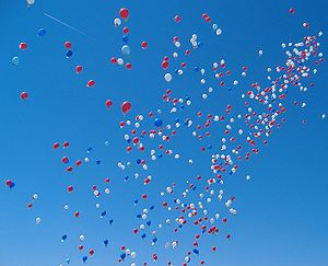 Dozens of balloons against a dark blue sky.
