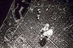 Photo en noir et blanc de la ville vue d'en haut.  La fumée d'une bombe peut être vu