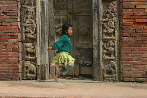 A girl is rope skipping in front of an old doo...