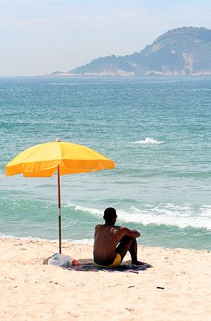 Man sitting under a beach parasol