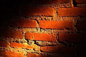 A brick wall partially illuminated by a ray of...