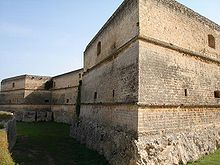 A three-storey stone structure with smooth walls and a roughly cut base. The walls are angular and have openings.