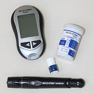 A Glucose Meter (Accu-Chek Aviva) with test st...