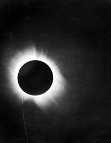 Black circle covering the sun, rays visible around it, in a dark sky.