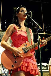 A brunette female in a red dress strums a guitar and sings into a microphone while performing on stage.