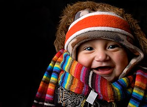 A laughing baby under winter clothes