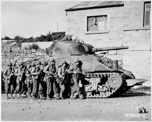 Yanks of 60th Infantry Regiment advance into a Belgian town under the protection of a heavy tank.
