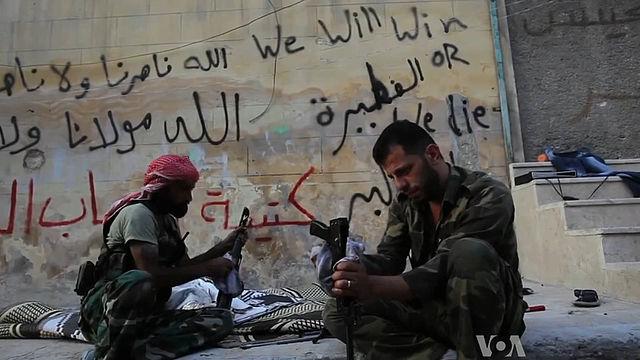 Miliziani siriani che puliscono il kalashnikov