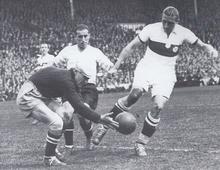 Le gardien accroupi attrape la balle sous les regards du défenseur. L'attaquant adverse ne peut récupérer le ballon et inscrire un but.