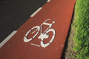 English: A red bike lane on the side of a high...