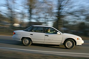 English: A woman driving a white Ford Taurus w...