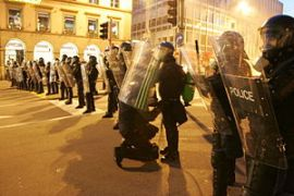 English: Policeman in riot control gear checki...