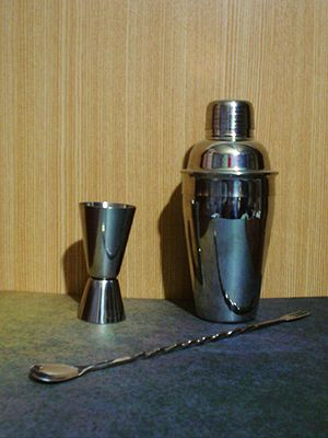 Cobbler shaker (right), jigger, and a bar spoon.