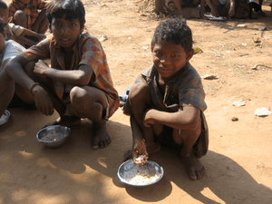 English: Children eating lunch outside their s...