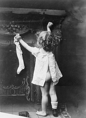 English: Little girl hanging up stocking by fi...