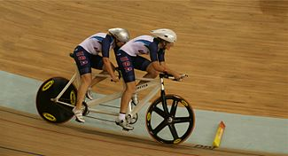 Dois atletas, usando capacete e uniforme dos Estados Unidos, pedalam na mesma bicicleta.