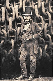 A 19th-century man wearing a jacket trousers and waistcoat, hands in pockets, cigar in mouth, wearing a tall stovepipe top hat, standing in front of giant iron chains on a drum.