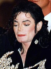 Close-up of a pale skinned Jackson with black hair. He is wearing a black jacket with white designs on it.
