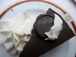Sachertorte with whipped cream and chocolate disc