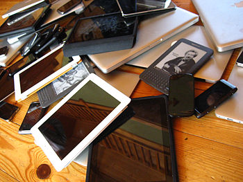 English: A pile of mobile devices including smart phones, tablets, laptops and ebok readers.