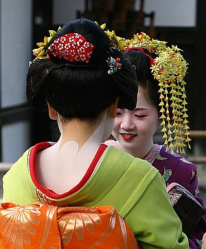 2 Maiko (apprentice Geisha) conversing near th...