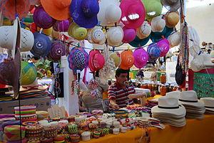 English: Vendor selling handcrafted hats and m...