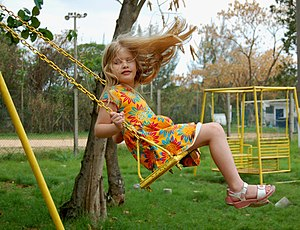 A girl on a garden swing. Original caption: : ...