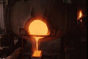 English: Pouring molten gold into ingot mold a...